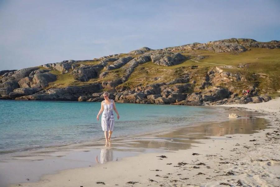 A woman walking on a beach in Scotland North Coast 500