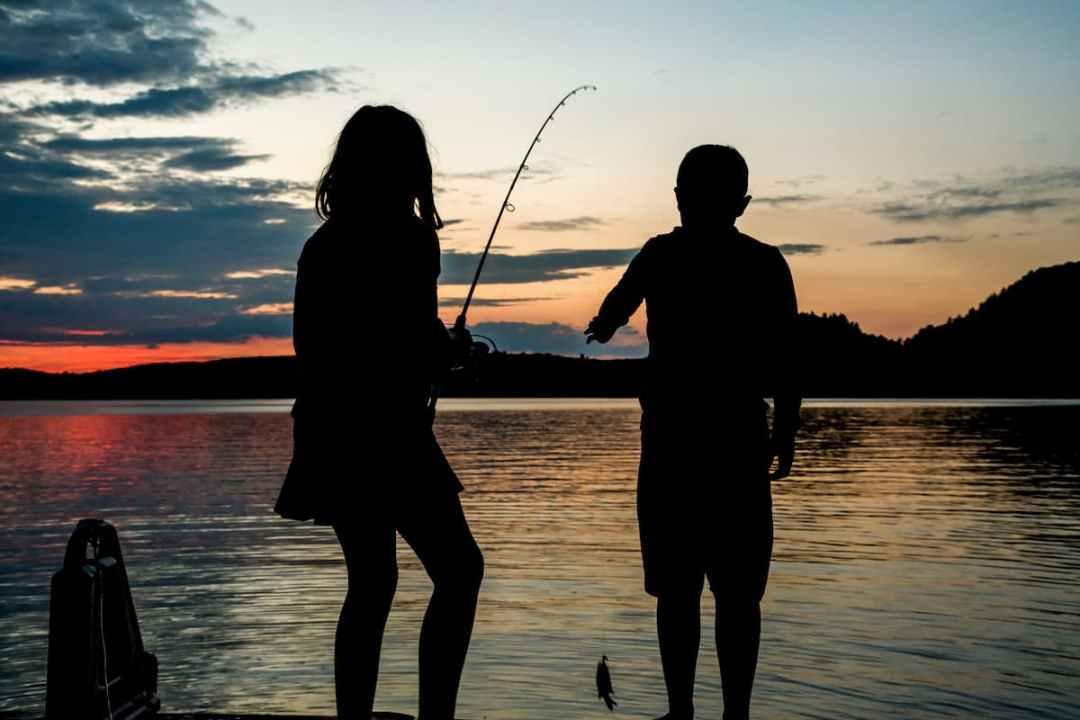 Two children fishing at dusk near Westport.
