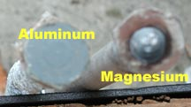 An aluminum anode with a flat hex head next to a magnesium anode with a hex head with a bump