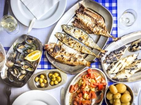 Gegrillter Fisch mit Salat, Kartoffeln, Oliven und Wein zählt zu den Klassikern auf Portugals Speisekarten.