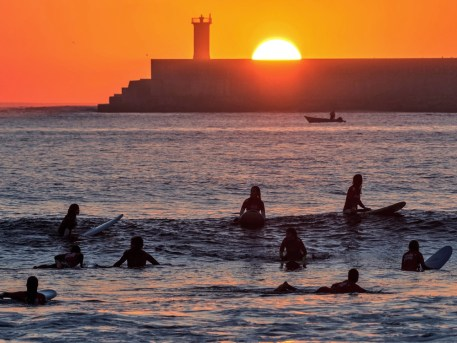 Surfer bei Sonnenuntergang am Stadtstrand von Porto