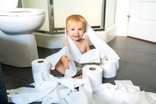 Toddler sitting on bathroom floor covered in toilet paper that has been unrolled