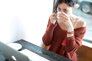 woman drinking coffee facing laptop