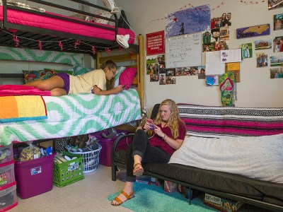 Two female students on their phones hanging out in their room in Reynolds Hall.
