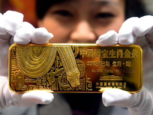 Chinese woman holding a gold bar