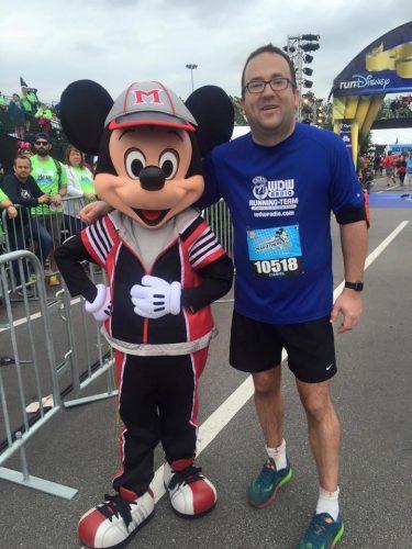 "alt=""Daniel Mulka and Mickey Mouse at the WDW Marathon finish line."""