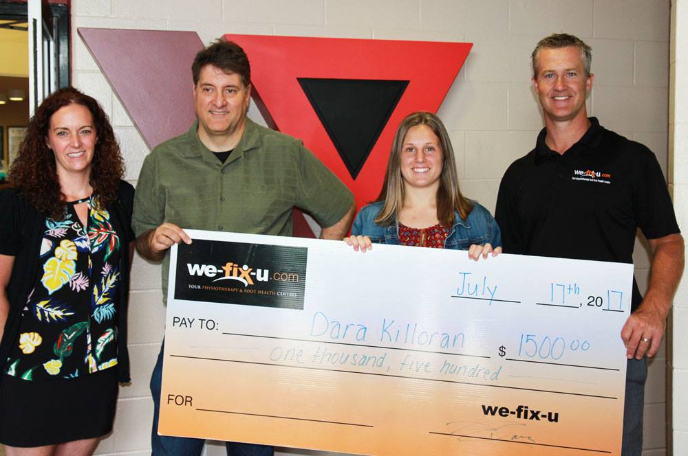 scholarship presentation four people holding a big cheque