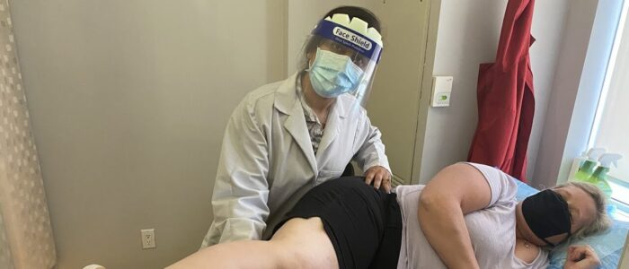 Physiotherapist wearing a face shield helping a patient relief pain on the bed