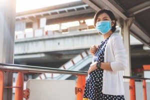 A photo of a pregnant woman, wearing a face mask, in a city