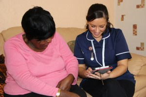 Nurse and patient talking while using technology