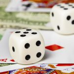 Pair of Dice on cards and money