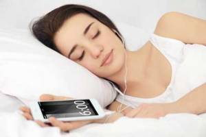 woman sleeping with earbuds and smartphone