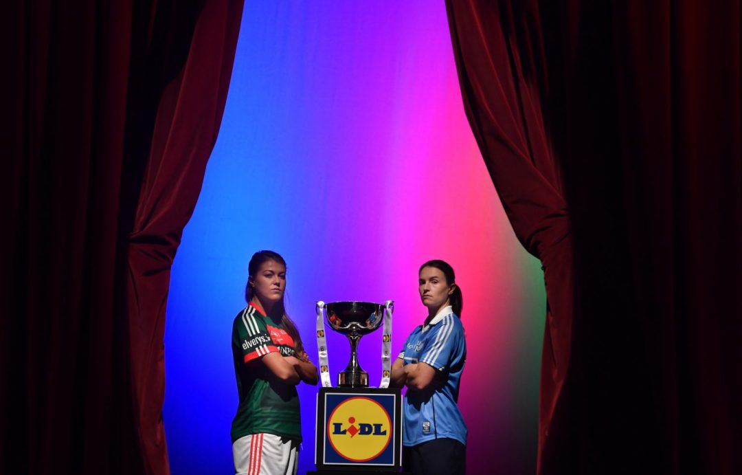 Dublin Captain Sinead Aherne And Mayo's Sarah Rowe On the Helix Stage Between Two Red Curtains With The Division 1 League Trophy