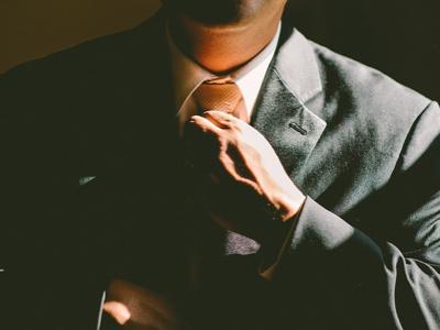 Man straightening tie when wearing a suit