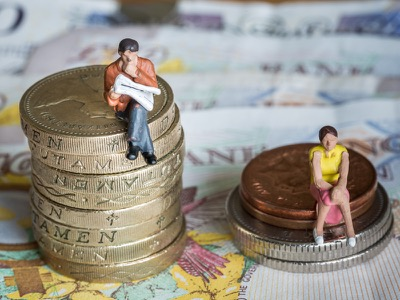 man-and-woman-sat-on-money-piles-gender-pay-gap-featured