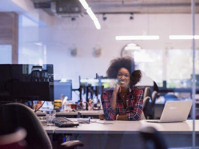 black business woman sitting at her desk featured