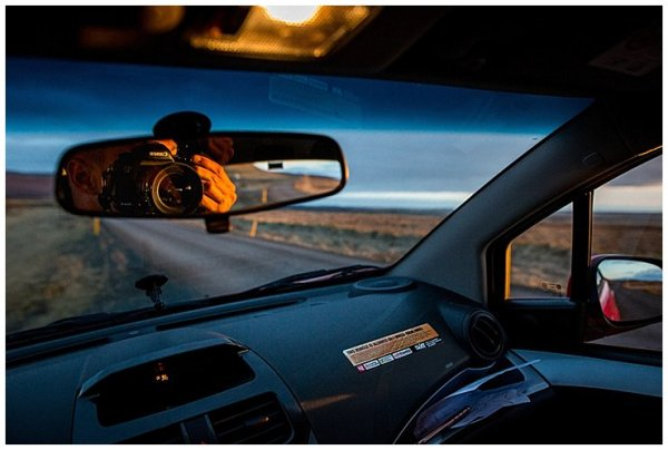 A reflection of a canon camera in the car's rear view mirror in Iceland