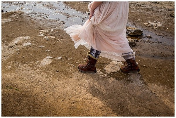 Anna walks across the dirt in Iceland in a pink floaty dress