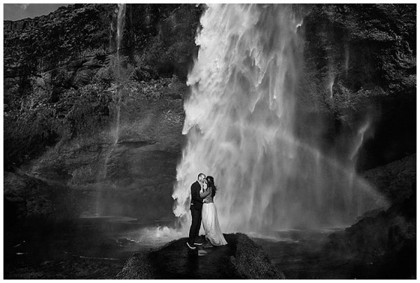 Anna and Mike embrace in front of a large waterfall in Iceland