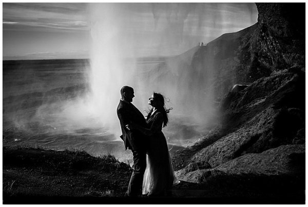 A black and white image of Anna and Mike embracing in front of Seljalandsfoss waterfall in Iceland