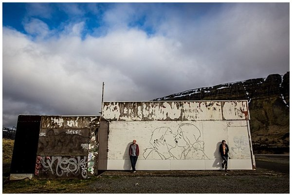 Anna & Mike lean against an old graffiti wall in Iceland