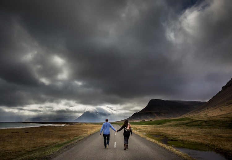 A honeymoon project in Iceland by Luna Weddings Mike and Anna walk down a road in Iceland holding hands