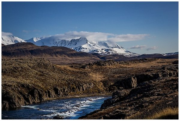 A river flows across Iceland with snowy mountain peaks in the distance