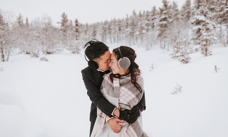 Finland Wedding couple embrace in the snow wearing blankets to keep warm by Maria Hedengren Photography