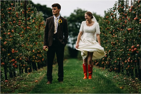 An English cricket club wedding the bride and grrom walk through the surrounding orchards and the bride wears red hunter wellington boots by Hannah Hall Photography
