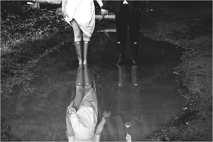 Bride and groom stand in a puddle at their English wedding by Hannah Hall Photography