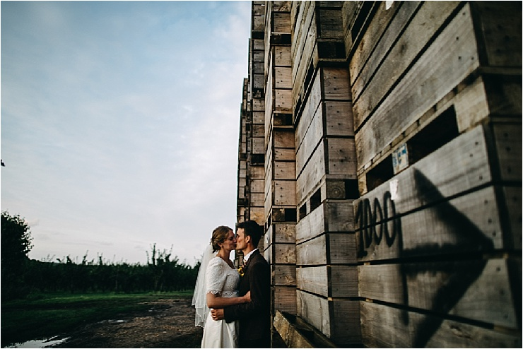 Bride and groom share a kiss in front of crates of Apples by Hannah Hall Photography