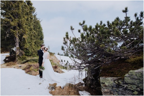 Austria mountain honeymoon shoot in Austria Susana & Tiago stand in the snow and embrace on a mountain in the Zillertal by Wild Connections Photography