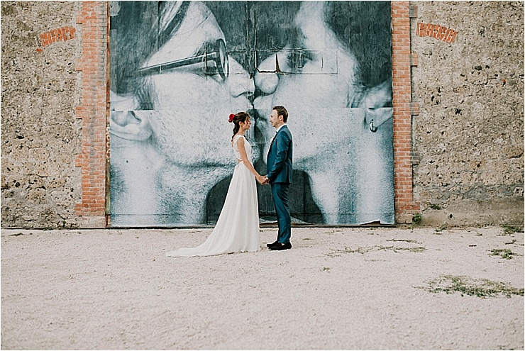 The bride and groom stand face to face holding hands in front of a giant poster of 2 people kissing at Borgo di Tragliata by Michele Abriola