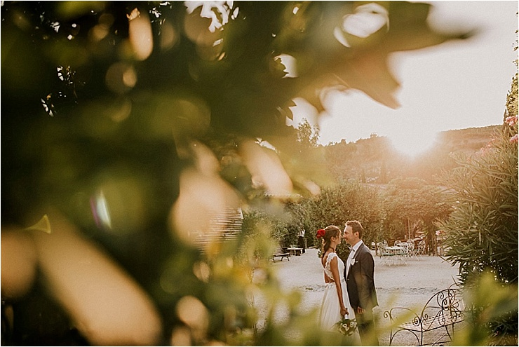 A picture of the bride and groom at unset taken through the leaves at Borgo di Tragliata by Michele Abriola