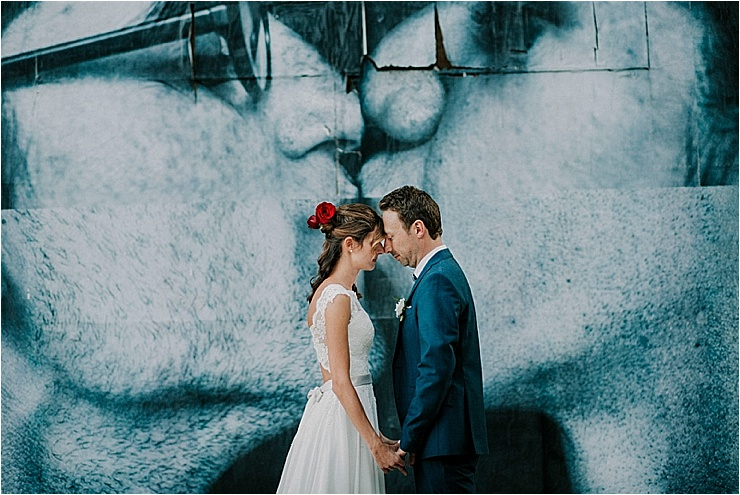 The bride and groom stand with their heads together in front of a large poster at Borgo di Tragliata by Michele Abriola