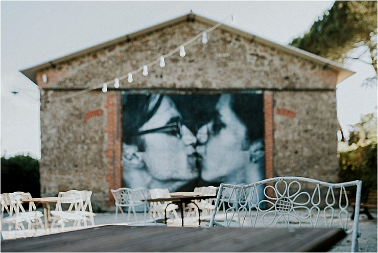 A large painted wall at Borgo di Tragliata with two people kissing painted on it by Michele Abriola