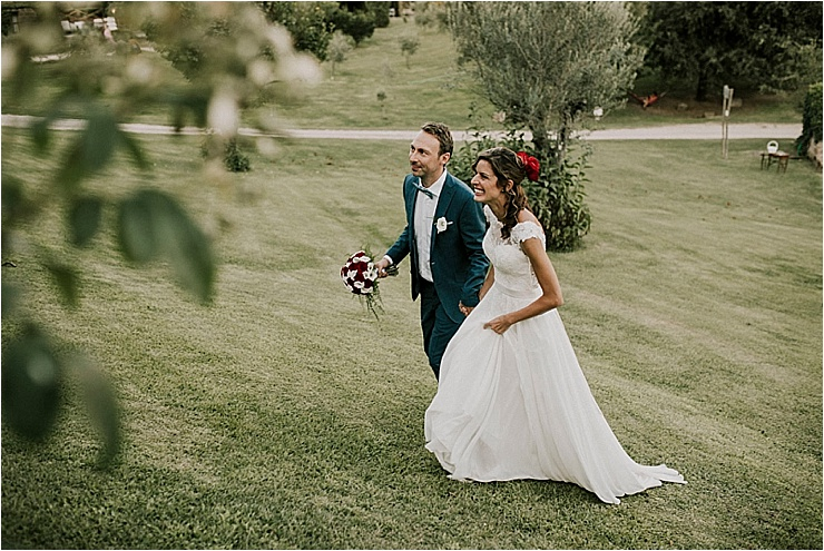 The bride and groom leave the ceremony and walk across the garden at Borgo di Tragliata by Michele Abriola