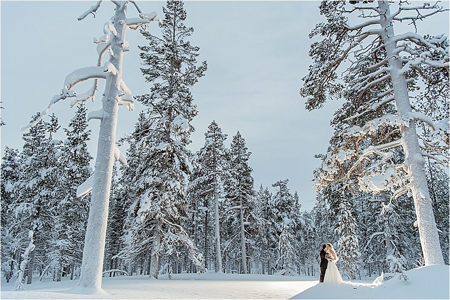 The bride and groom stand as small figures against at snowy landscape after their lapland elopement at Kakslauttanen arctic resort in Finland by Your Adventure Wedding