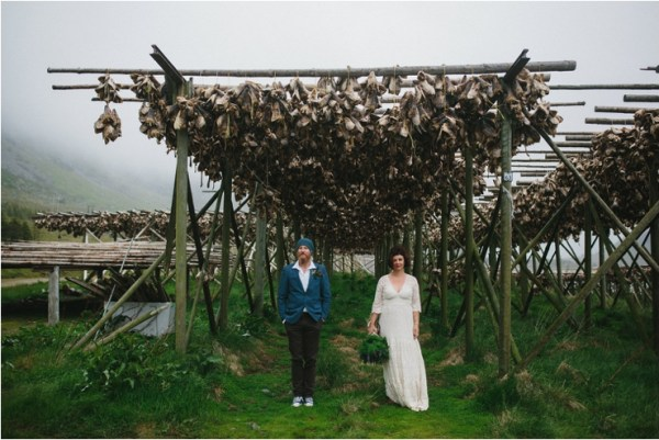 Bride and groom pose under a wooden frame with fish hung on it in Lofoten Norway by Thomas Stewart