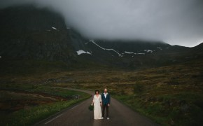 Bride and groom stand on a foggy road in Lofoten Norway by Thomas Stewart