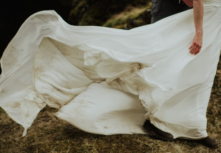 A dirty wedding dress blows in the wind in Iceland by Wild Connections Photography