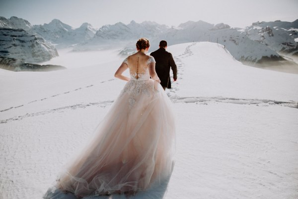 Couple walks through snow by Delia Folghera Photography