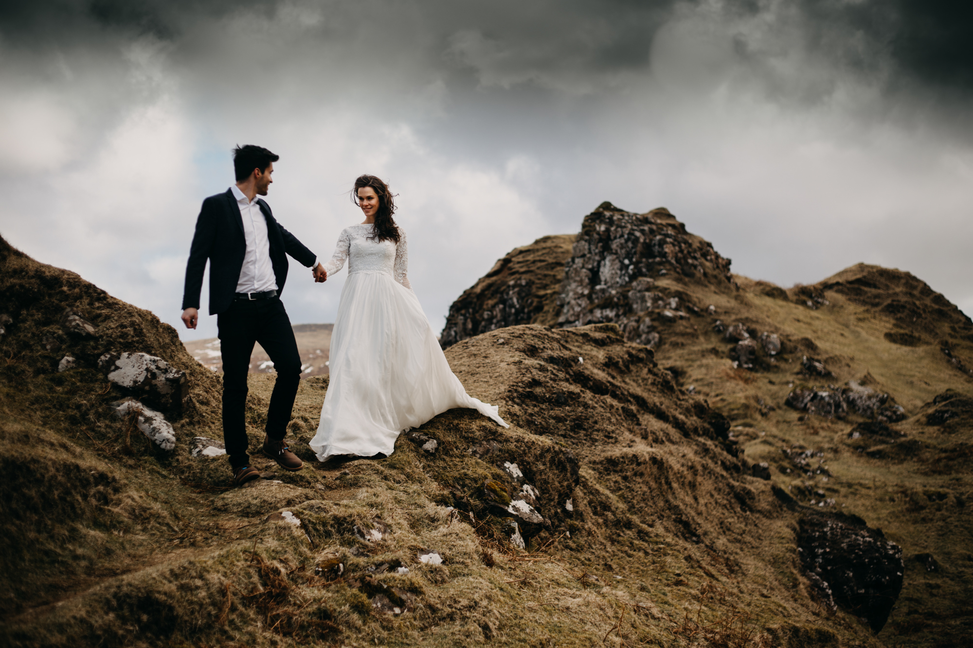 Bride and groom walking over mountain trail by Unfurl Photography