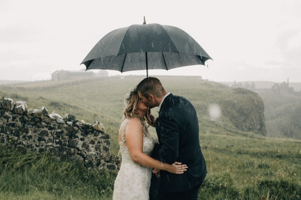 Bride and groom kissing under an umbrella in heavy rain by Paula O'Hara