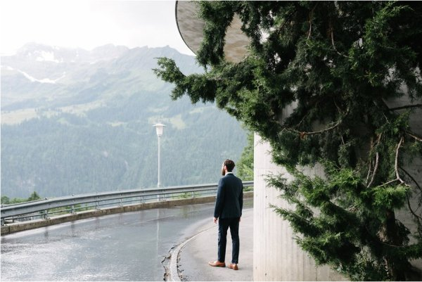 Groom hides from the rain under a railway bride - After wedding honeymoon shoot in Wengen by Caroline Hancox Photography