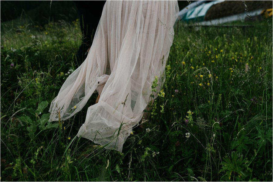 The dress train drags on the ground through the grass - After wedding honeymoon shoot in Wengen by Caroline Hancox Photography