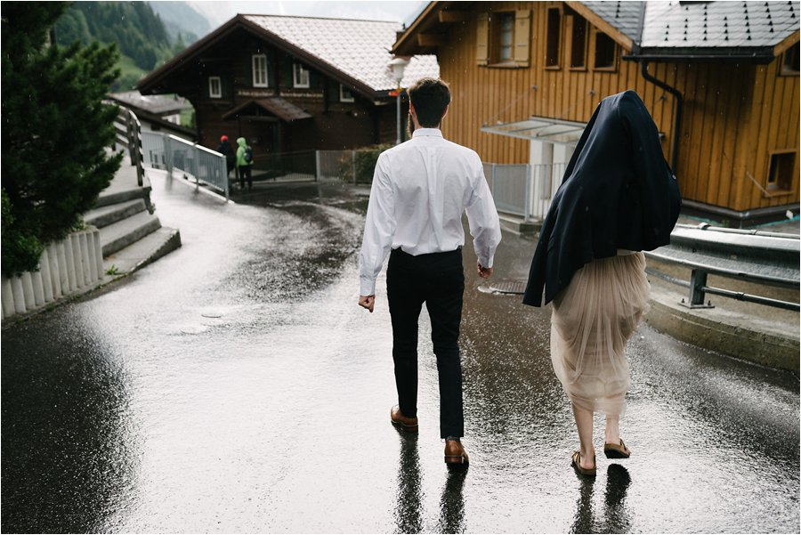 Bride protects herself from the rain by putting the groom's jacket over her head - After wedding honeymoon shoot in Wengen by Caroline Hancox Photography