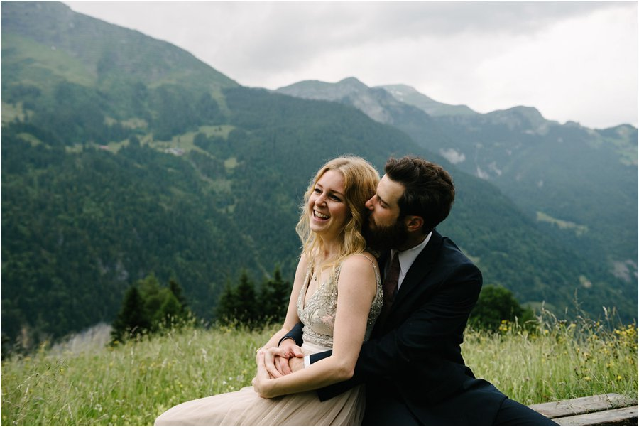 Groom embraces the bride while sitting on a bench with mountain views - After wedding honeymoon shoot in Wengen by Caroline Hancox Photography