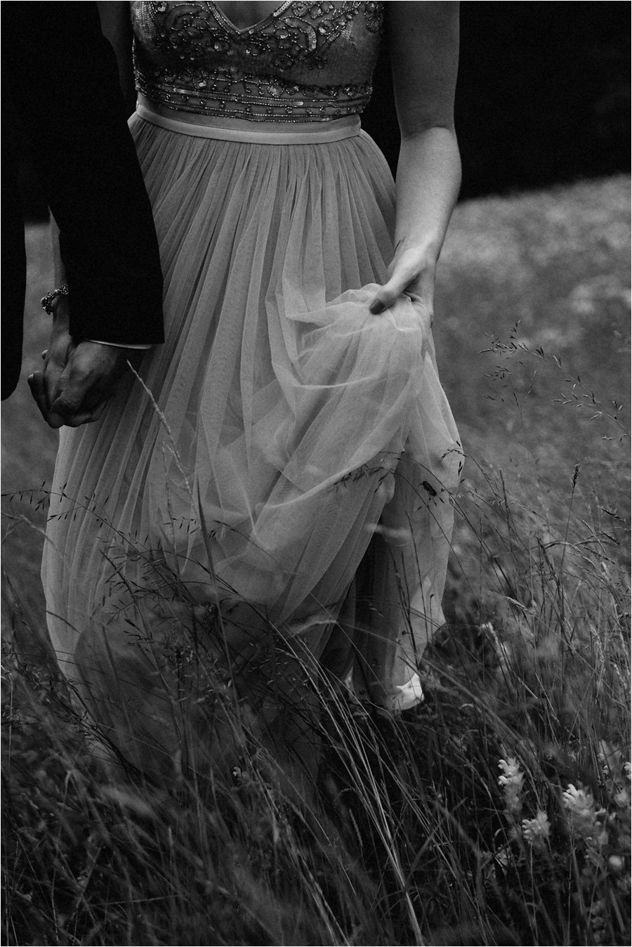 The bride holds up the front of her BHLDN dress as she walks through the long grass - After wedding honeymoon shoot in Wengen by Caroline Hancox Photography