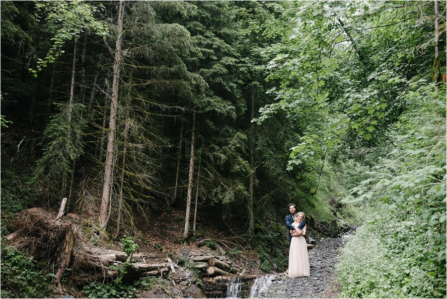 Bride and groom standing at the top of a waterfall in a forest - After wedding honeymoon shoot in Wengen by Caroline Hancox Photography